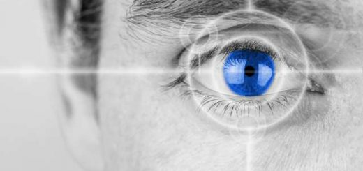 Vision concept with a greyscale image of a mans eye with a crosshair focused on his iris which has been selectively colored blue.